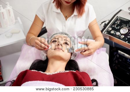 Doctor with ultrasonic scraber does the ultrasound cavitation facial peeling for woman. Procedure of ultrasonic cleaning of face. Cosmetological clinic. poster