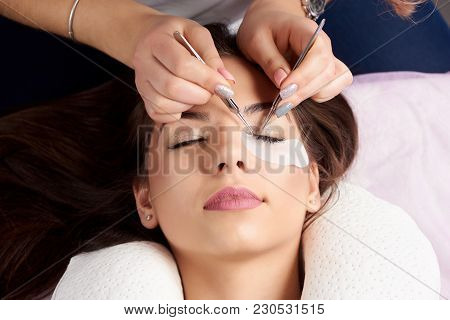 Close-up Of The Hands Of A Beautician With Tweezers In The Hands In The Process Of Eyelash Extension