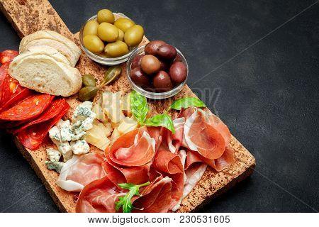 Italian Prosciutto Crudo Or Spanish Jamon, Cheese, Olives And Bread. Raw Ham On Cork Cutting Board.