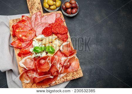 Italian Prosciutto Crudo Or Spanish Jamon, Cheese And Olives Raw Ham On Cork Cutting Board. Concrete