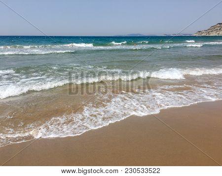 Water Texture In The Mediterranean Sea Coast Shore. Island On The Sea Beach. Texture Of The Sea Wate