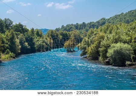 View To A Beautiful Natural Blue River In Front Of Green Nature. Close-up Of A Flowing Blue River Su