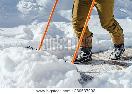 A Man Cleans The Snow With A Large Shovel Scraper In Front Of His Country House