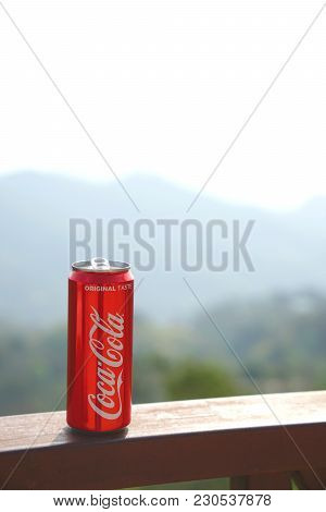 Chiang Rai, Thailand, Febuary 18, 2018 : Classic Red Coca-cola Can With Background Of Mountain Layer