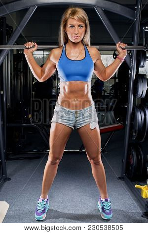 Girl Standing On The Smith Machine In The Gym In A Denim Shorts And Blue Top