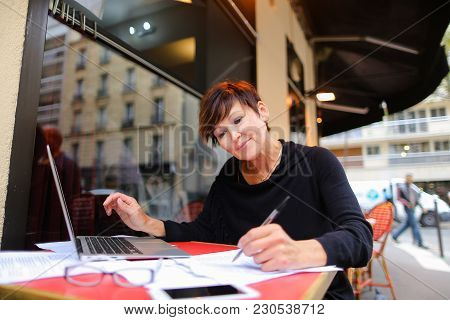 Female Accountant Sitting At Outdoor Cafe With Laptop And Making Finance Account. Lady Dressed In Bl