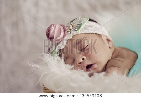 Portrait Of Cute And Adorable Newborn Baby With Floral Head Band Sleeping In Basket Covered With Fur
