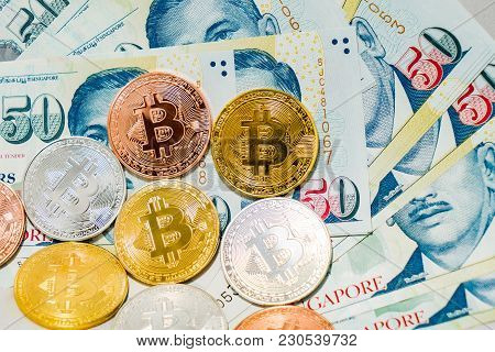 Singapore Dollar Banknotes And Bitcoin Cryptocurrency Coins On White Background