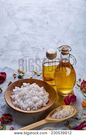 Spa Concept: Composition Of Spa Treatment With Natural Sea Salt, Aromatic Oil And Flowers On Light B