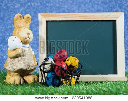 Many Colorful Of Easter Eggs Placed In Front Of Blackboard With Easter Rabbit. Blackboard With Color