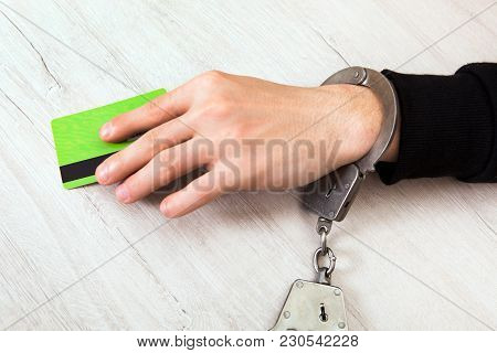 Person In Handcuffs With A Bank Card On The Table Closeup