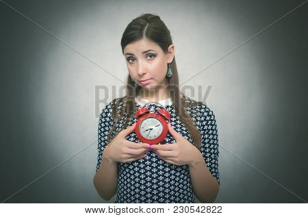 Guilty Look Woman Holding In Hands Alarm Clock And Hides Her Eyes. Latecomer Student Or Emloyee. Be