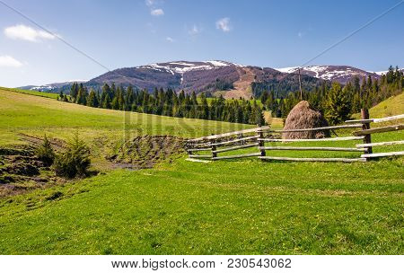 Beautiful Rural Scenery In Springtime. Wooden Fence And Haystack On A Grassy Hillside At The Foot Of