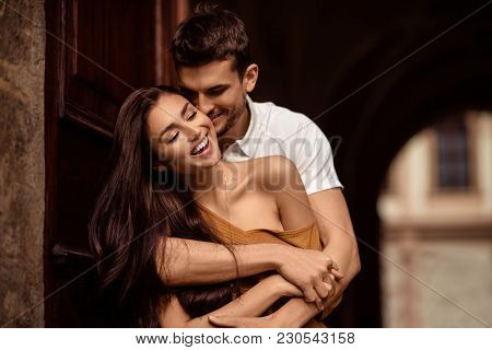 Happy Young Female With Long Dark Hair Glad To Recieve Passionate Kiss From Her Boyfriend. Handsome