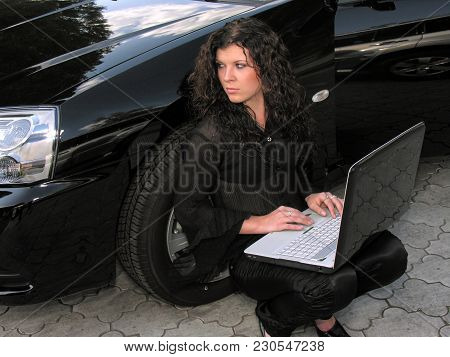 Young Woman With Laptop Sitting Near The Car