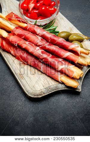 Traditional Italian Snack Prosciutto Crudo Or Jamon Bread Sticks, Peppers And Capers On Wooden Cutti