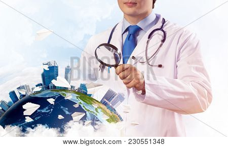 Conceptual Image Of Confident Industry Employee In White Suit Looking On The Earth Globe Through Mag