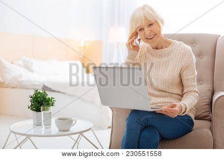 Progressive Pensioner. Smart Positive Excited Pensioner Feeling Happy While Sitting In A Nice Comfor