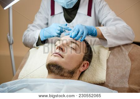 Man Lay Down At Clinic Couch While Doctor Put Injector To His Forehead