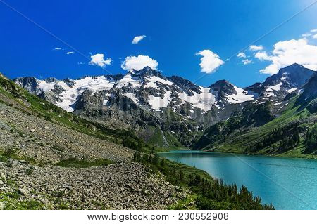Mountain Lake, Russia Siberia Altai Mountains. Beautiful Mountain Slope With Scattered Rocks On The