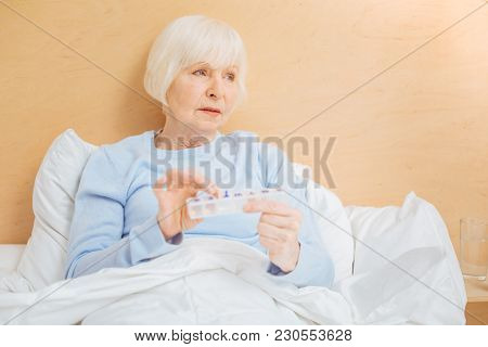 Useful Box. Calm Serious Aged Woman Feeling Bad And Looking Into The Distance While Staying In Bed W