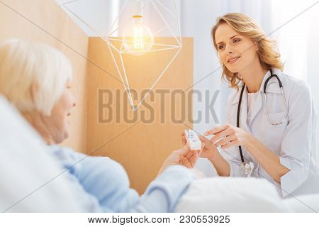 Attentive Doctor. Pleasant Polite Experienced Doctor Looking Kindly At Her Ill Aged Patient And Smil