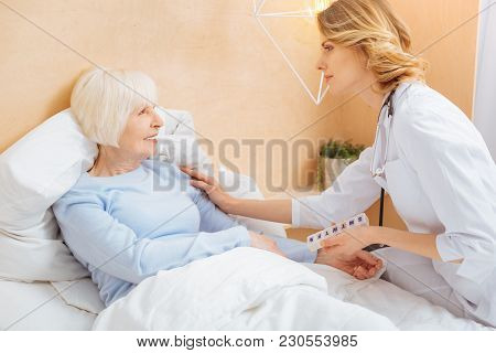 Please Relax. Smart Experienced Reliable Doctor Touching The Shoulder Of An Ill Positive Senior Woma
