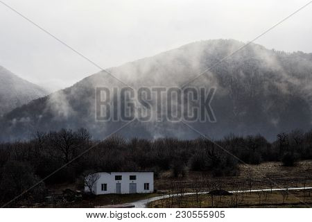 Beautiful Landscape Of Mountains And Forest With Village Building Or Old Abandoned Ruined Brick Hous