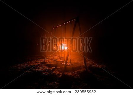 Night Photo Of Metal Swing Standing Outdoor At Night Time With Fog And Surreal Toned Light On Backgr