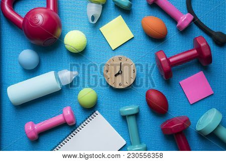 Time For Exercising Clock, Dumbbell And Fitness Equipment With Yoga Mat Background