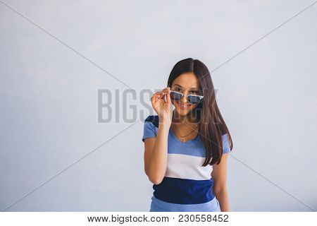 Latino Woman Wearing Casual Clothes Looking Through Sunglasses And Smiling, While Standing Against B