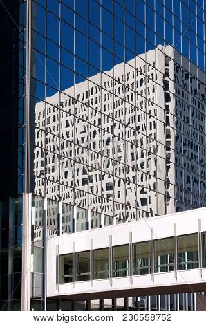 Modern Architecture Of Office Tower With Reflections Of Another Building On Glass Exterior And Skywa