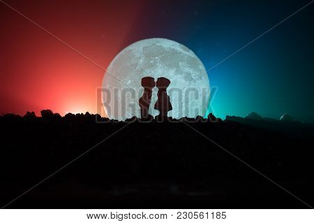 Silhouette Of Couple Kissing Under Full Moon. Guy Kiss Girl Hand On Full Moon Silhouette Background.
