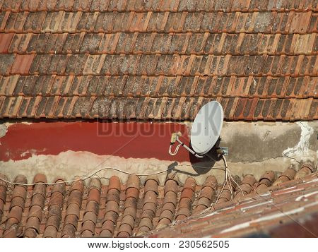 Isolated Satellite Dish On Old Shingle Roof