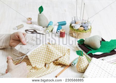 Hands Of The Needlewoman Hold Scissors And Cut Out A Piece Of Pattern For A Handmade Toy