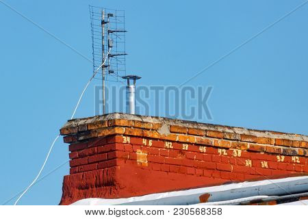 Universal Antenna For Receiving Analog Tv Signal Is Installed On The Roof Of A Brick House