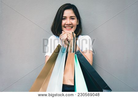 Young Happy Summer Shopping Asian Woman With Shopping Bags On Grey Background At Copy Space. Beautif