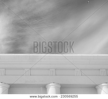Facade in classical style. Antique style building. White building. Architectural background.White facade. Monochrome.