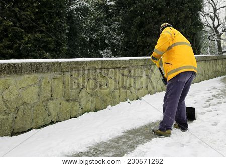 Garbage Man Shovels The Snow From The Sidewalk After Snowfall