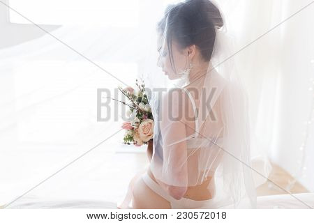 Beautiful Sexy Stylish Young Bride In Lingerie With Nice Bouquet Sitting On Bed Under Veil. Horizont