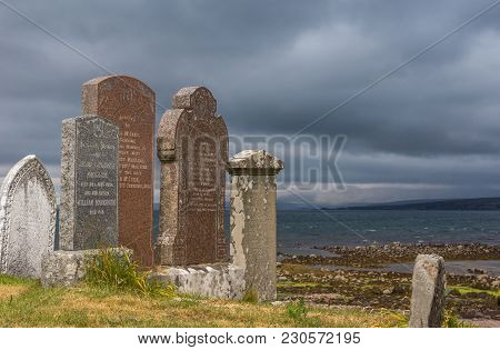 Laide, Scotland - June 8, 2012: Ruins At Laide Historic Beach Side Cemetery Under Dark Gray Heavy Cl