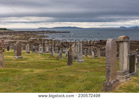 Laide, Scotland - June 8, 2012: Tomgstones At Laide Historic Beach Side Cemetery Under Gray-blue Hea