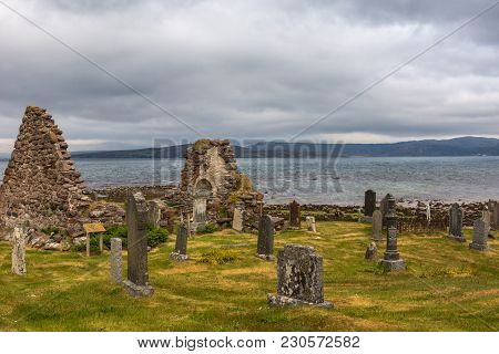 Laide, Scotland - June 8, 2012: Chapel Ruin At Laide Historic Beach Side Cemetery Under Gray-blue He
