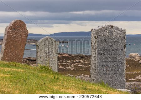 Laide, Scotland - June 8, 2012: Tombstone Closeup At Laide Historic Beach Side Cemetery Under Gray-b