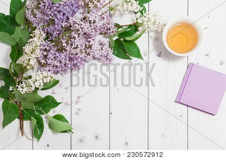 Beautiful White And Violet Lilac Flowers With Closed Note-book And Cup Of Tea On The White Wooden Ba