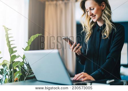 Young Smiling Businesswoman In Black Blouse Is Standing Indoor, Working On Computer While Using Smar