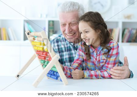 Grandfather Teaching His Granddaughter To Use Abacus Indoors
