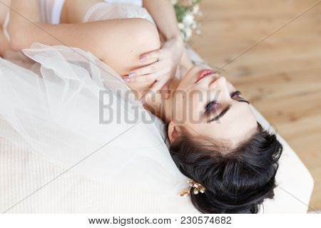 Side View Close Up Of A Beautiful Caucasian Woman In Sexy Lingerie Lying On Her Back With Outstretch