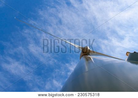 Wind Tubine Pylon From Bottom Against Blue Sky With Clouds