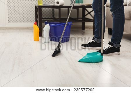 Unrecognizable Man Cleaning Home, Sweeping In Living-room. Housekeeping And Home Cleaning Concept